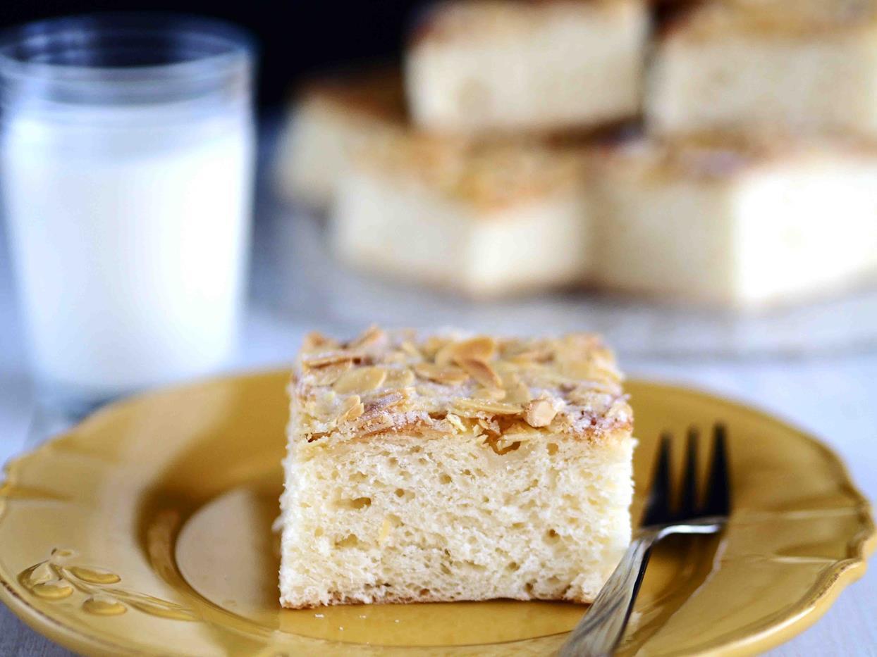 kawałek drożdżowego ciasta maślanego z migdałami na talerzyku, szklanka mleka w tle - wszystkiego słodkiego