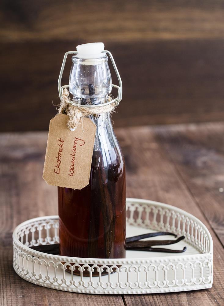 ekstrakt waniliowy w butelce z korkiem na białej tacy na stole - wszystkiego słodkiego