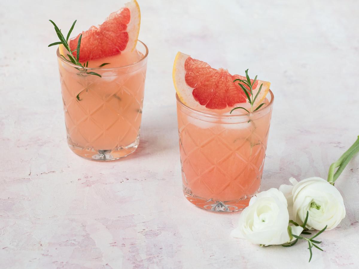 Lemoniada grapefruitowa z wanilią i rozmarynem w dwóch szklankach podana z kostkami lodu, cząstką grapefruita i łodyżką rozmarynu - Wszystkiego Słodkiego