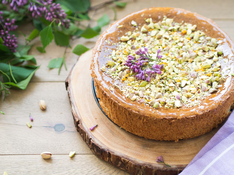 Ciasto migdałowo-pomarańczowe udekorowane posiekanymi pistacjami i kwiatami bzu