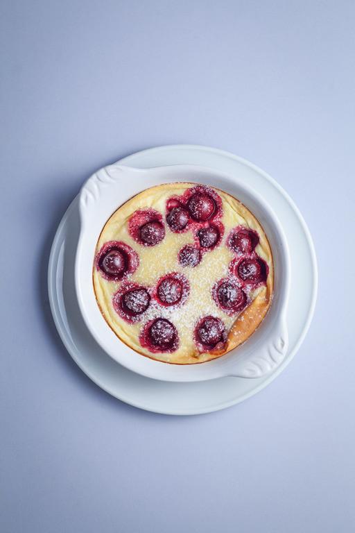 deser clafoutis z wiśniami w białej miseczce