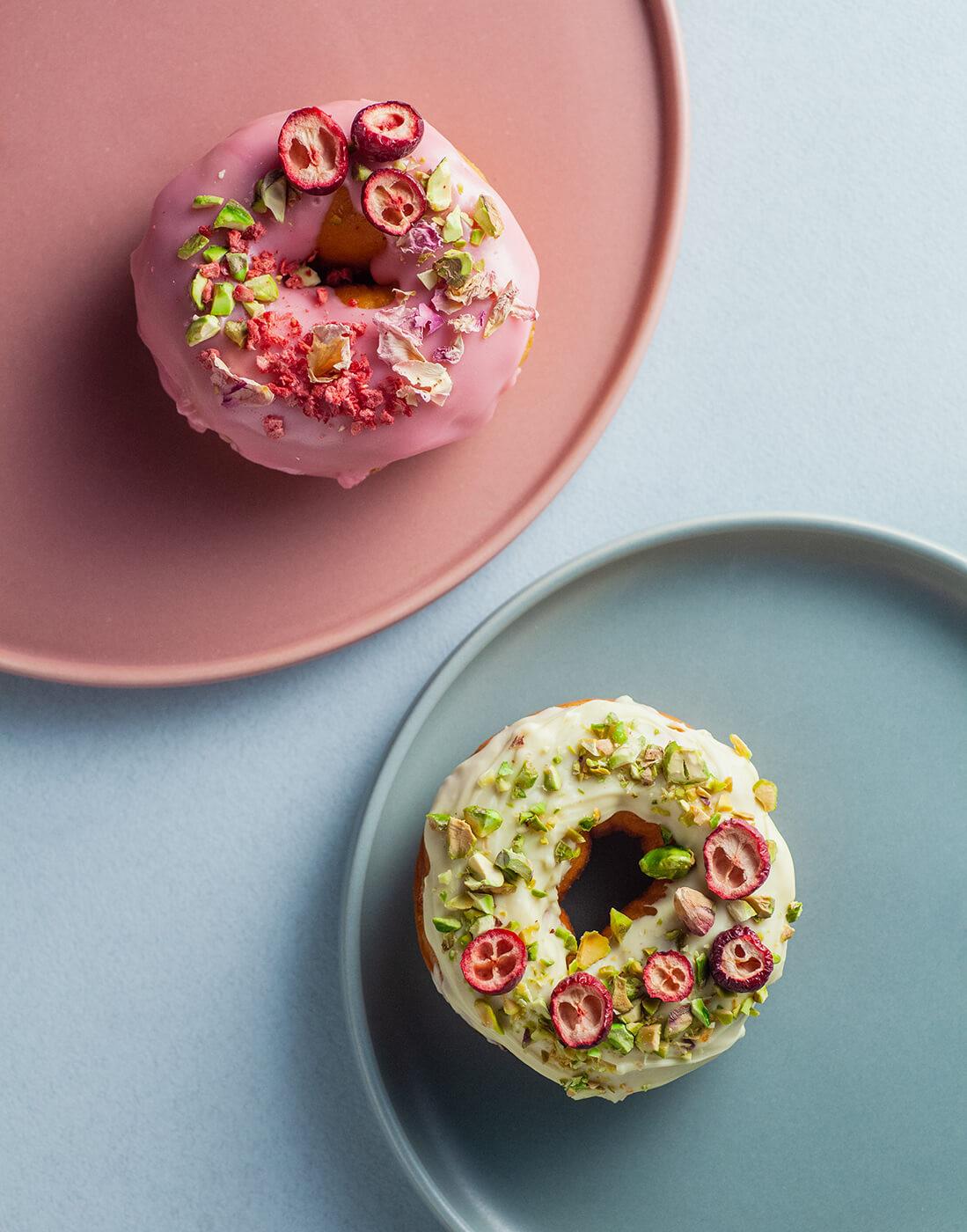 dwa donuty z kolorowym lukrem, pokruszonymi pistacjami i suszonymi owocami