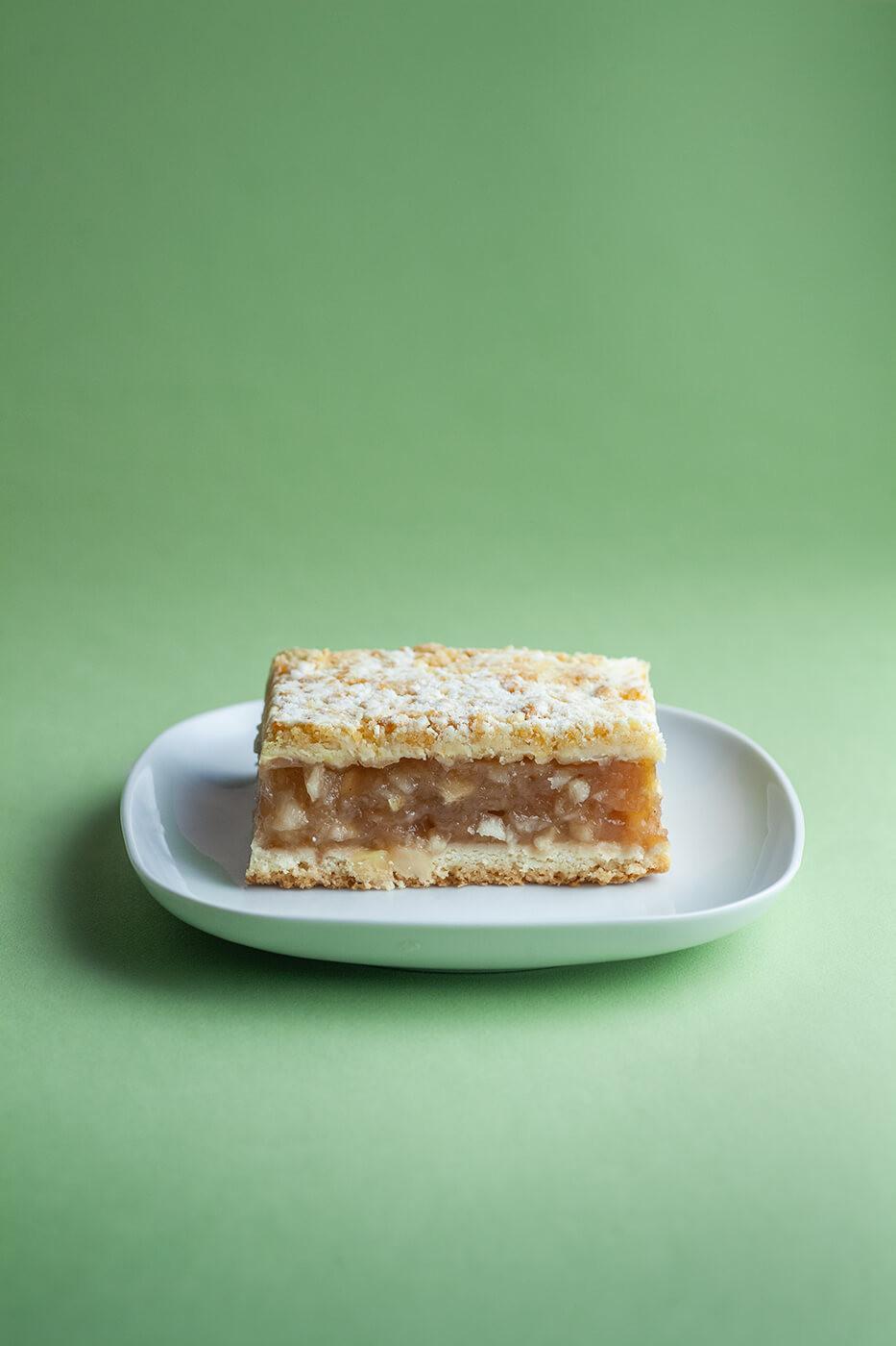 Kawałek jabłecznika na kruchym cieście posypany cukrem pudrem