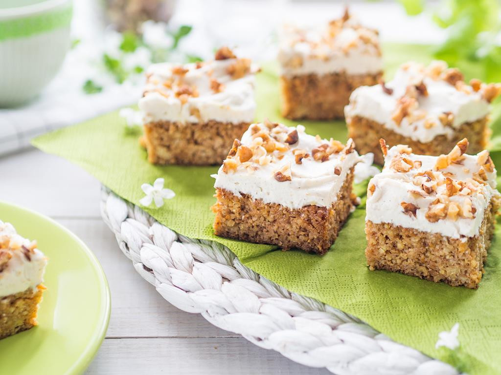 Ciasto marchewkowe jaglane podzielone na kawałki z polewą z serka mascarpone