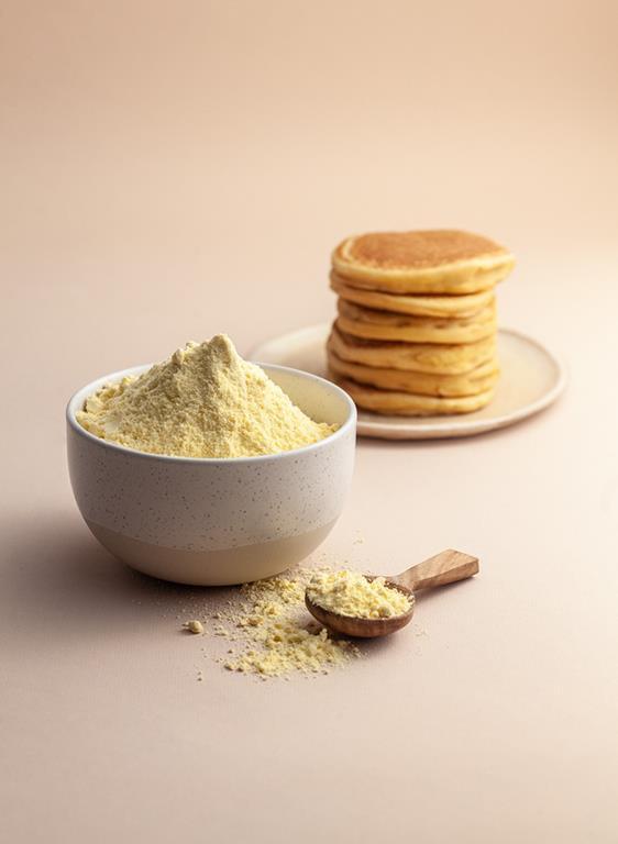 Mąka kukurydziana w miseczce i pancakes kukurydziane.
