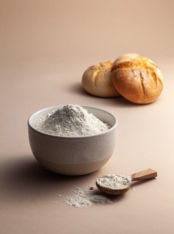 Mąka pełnoziarnista w miseczce i dwie bułki