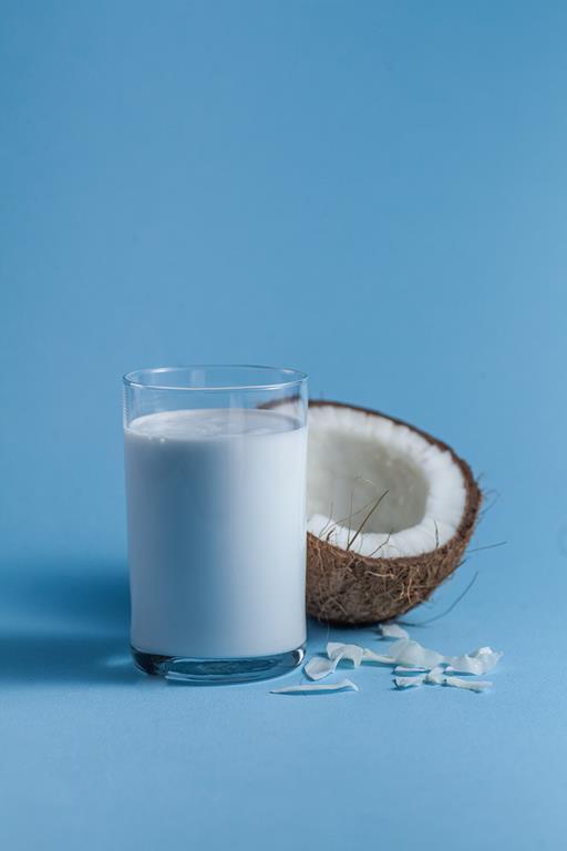 Mleko kokosowe w szklance. Obok rozłupany kokos.