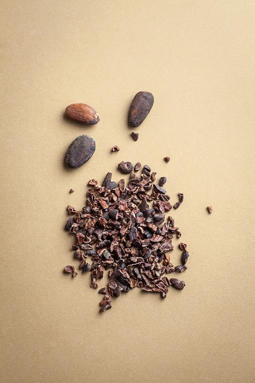 Garstka nibs na blacie - pokruszone, prażone ziarna kakaowca.