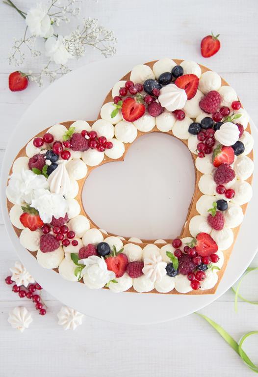 tort serduszko w kształcie serce z owocami i bitą śmietaną na talerzu