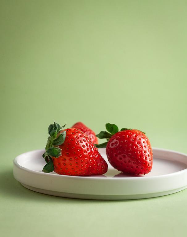 Trzy truskawki na białym talerzyku.