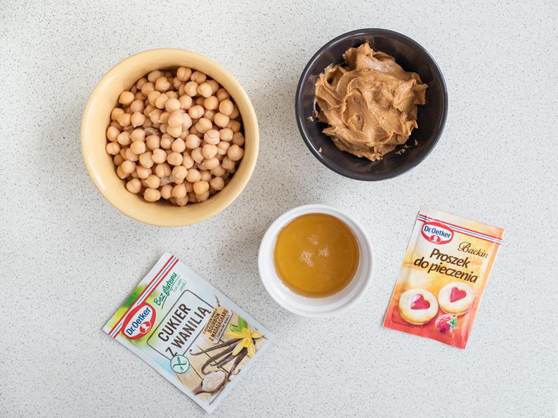 ciecierzyca, masło orzechowe, syrop z agawy w miseczkach, cukier z wanilią bez glutenu i proszek do pieczenia bez glutenu