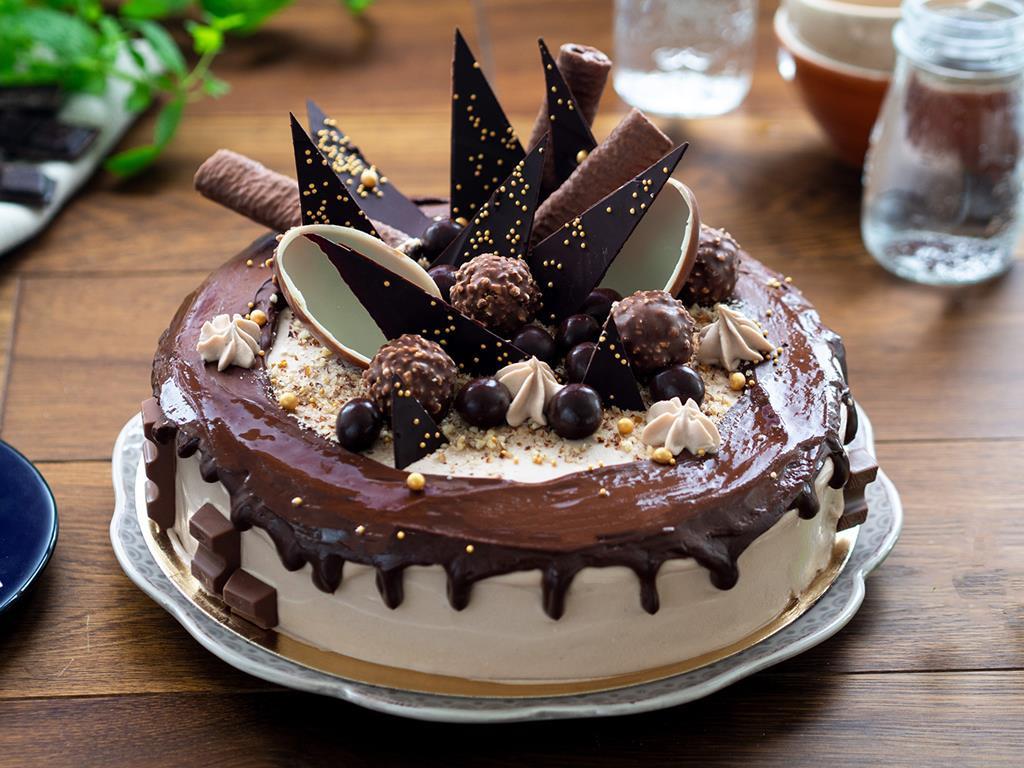 Czekoladowo-orzechowy tort Drip Cake na bazie biszkoptu kakaowego, przełożonego kremem czekoladowo-orzechowym ze zmielonymi orzechami laskowymi i polanego polewą czekoladową, tort ozdobiony jajkami czekoladowymi, posypką blask pereł dr. oetkera