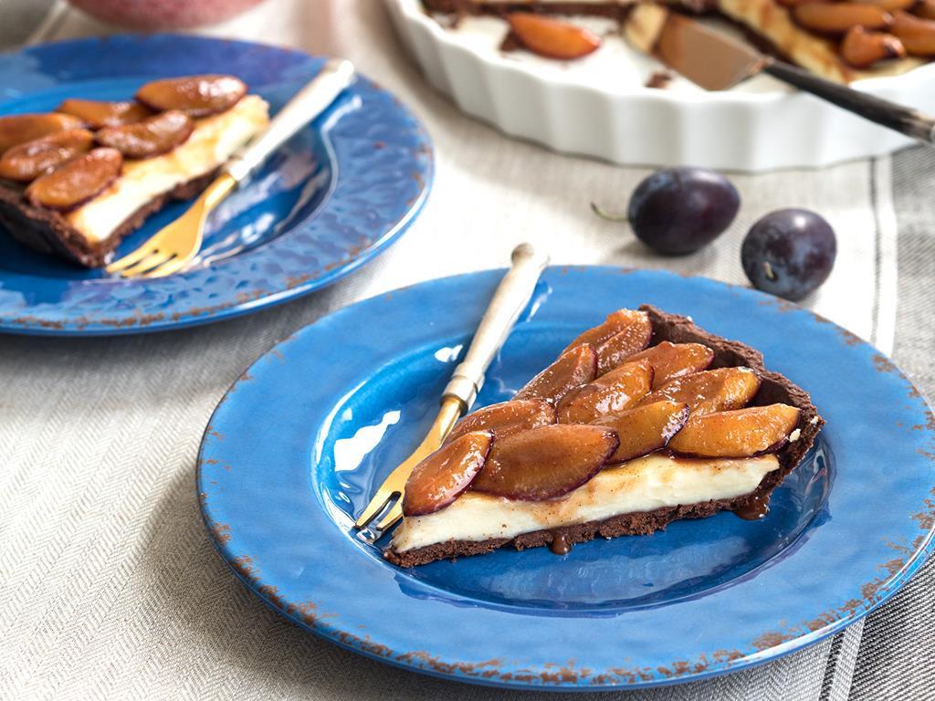 kawałek tarty z karmelizowanymi śliwkami na niebieskim talerzyku