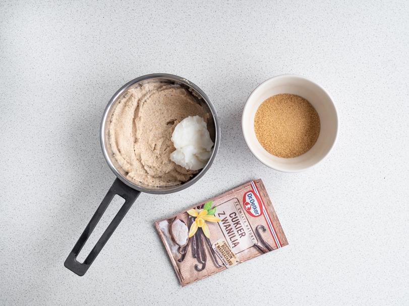 orzechowa masa i olej kokosowy w rondelku, cukier trzcinowy w miseczce i cukier z wanilią bez glutenu