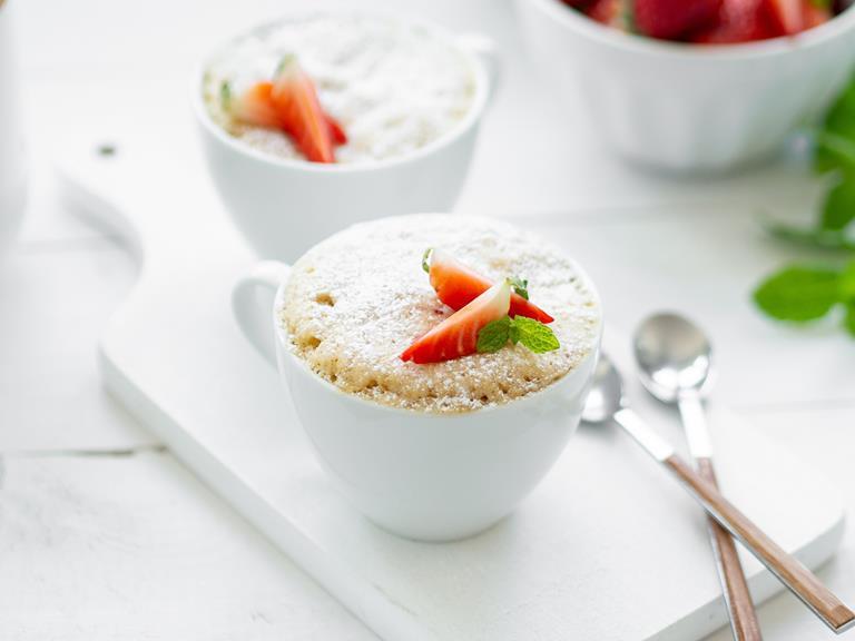 Ciasto waniliowe z truskawkami w dwóch filiżankach posypane cukrem pudrem i udekorowane świeżą truskawką - Wszystkiego Słodkiego