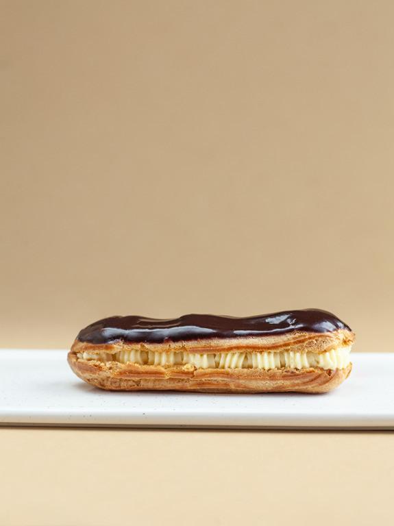 Ekler z z kremem polany czekoladą położony na białym talerzyku