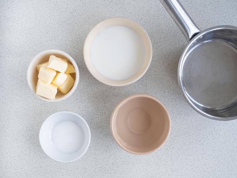mleko, woda, cukier masło w miseczkach, rondelek na blacie