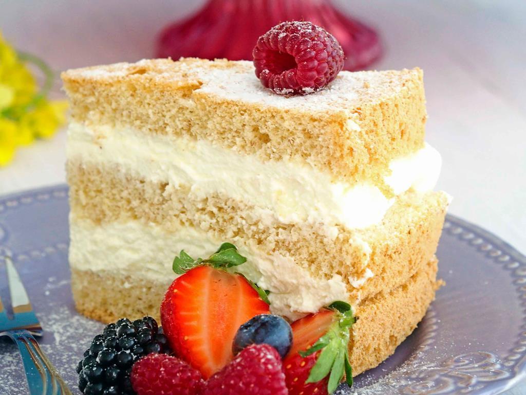 kawałek tortu na pełnoziarnistym biszkopcie z kremem śmietankowym i owocami