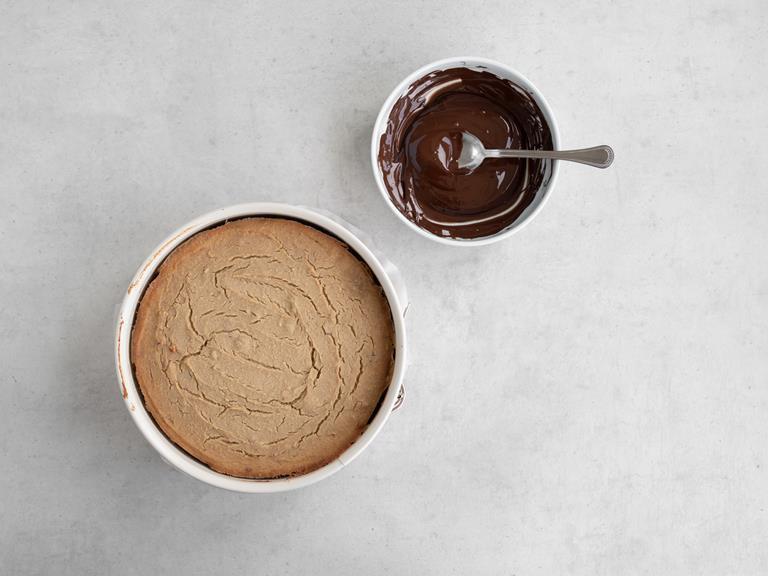 upieczone ciasto w tortownicy, polewa czekoladowa w miseczce