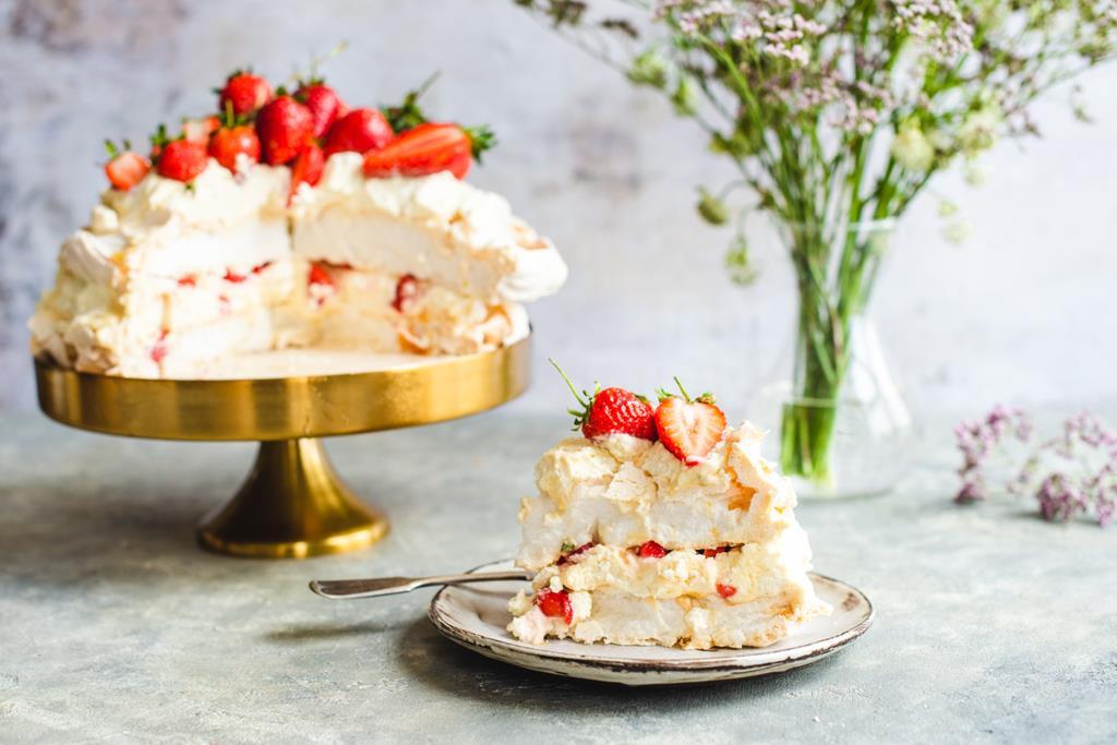 Kawałek tortu bezowego z truskawkami i bitą śmietaną