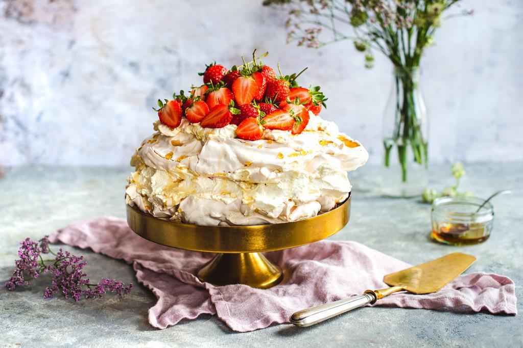 Tort bezowy z truskawkami, syropem klonowym i waniliową bitą śmietaną na paterze