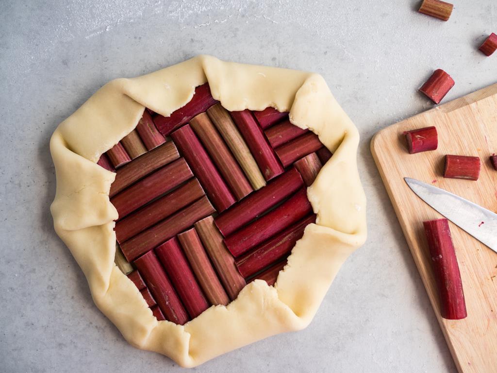 Rozwałkowane ciasto na galette wyłożone łodygami rabarbaru