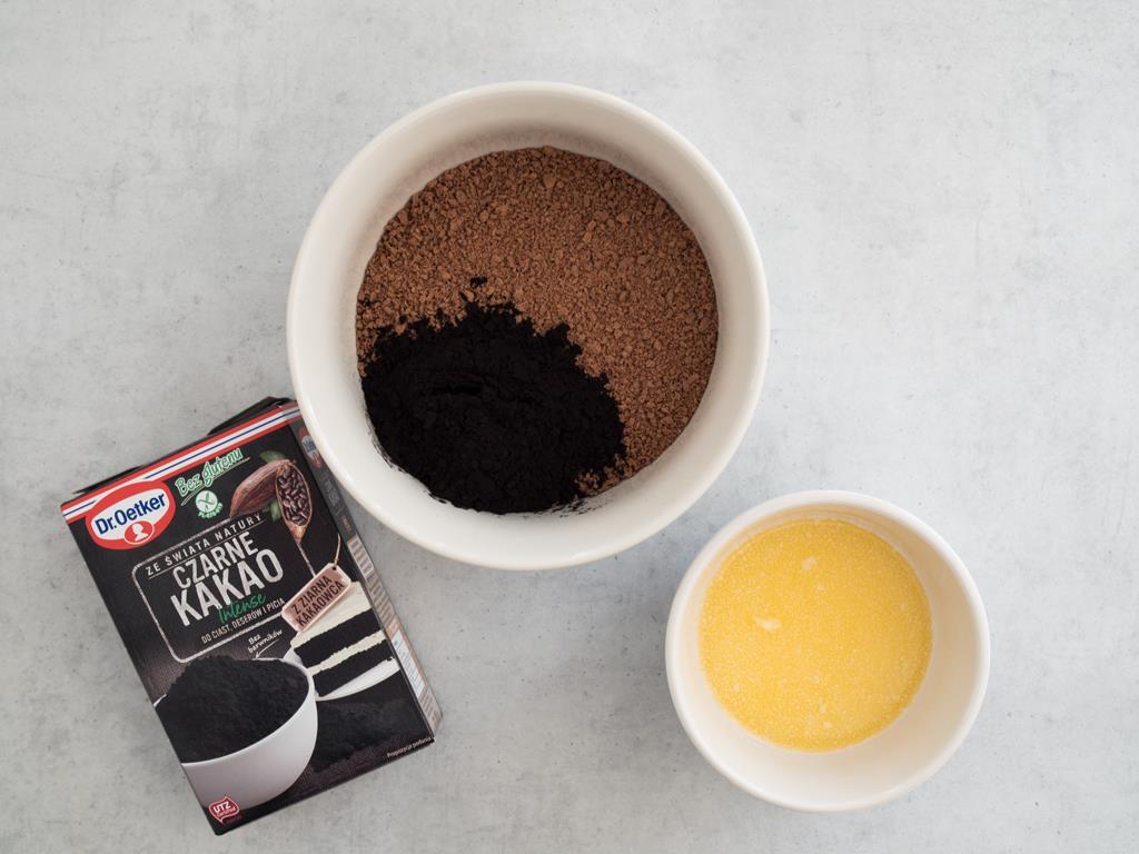 Czarne Kakao Dr. Oetkera z pokruszonymi herbatnikami w misce i masło w miseczce.