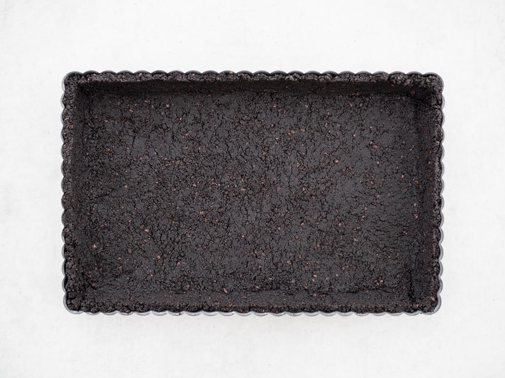 Kakaowe ciasto wyłożone na dno formy o wymiarach 18 x 28 cm