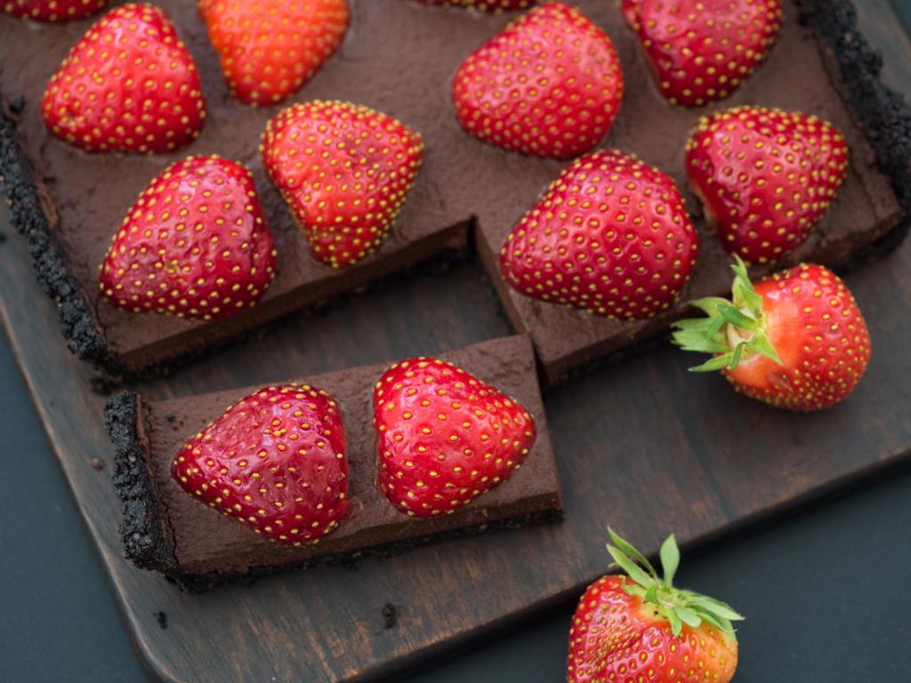 Intensywnie czekoladowa tarta z truskawkami z wyciętym kawałkiem położona na drewnianym blacie.