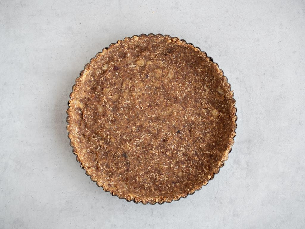 Spód formy do torty wylepiony masą daktylowo-migdałowo-kokosową