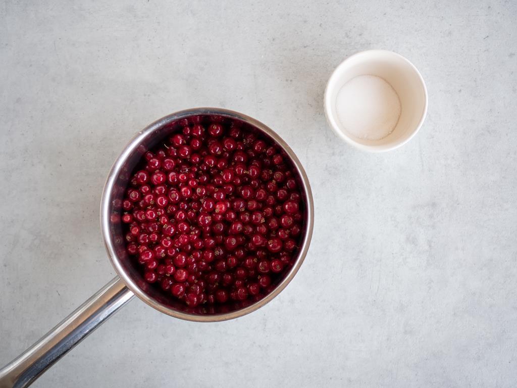 Czerwone porzeczki w garnuszku i cukier w miseczce.