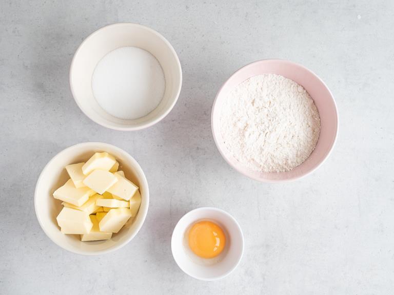 Mąka pszenna, masło, cukier i żółtko w osobnych miseczkach