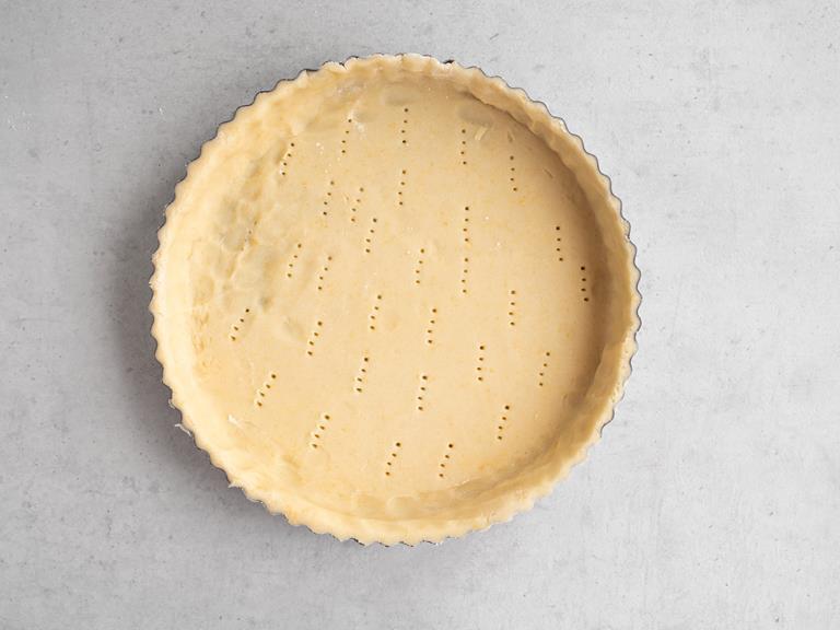 Forma do tarty wyłożona ciastem, które zostało nakłute widelcem
