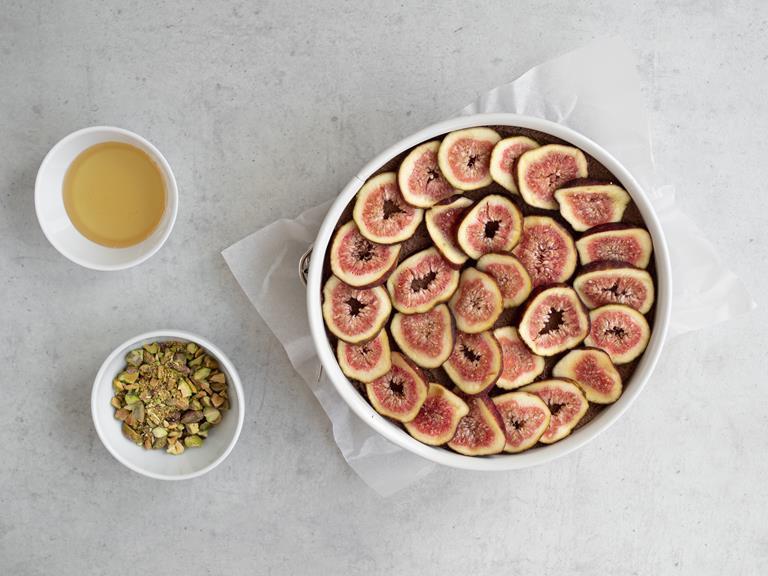 Tofurnik z figami w tortownicy z miseczką z pistacjami i syropem z agawy