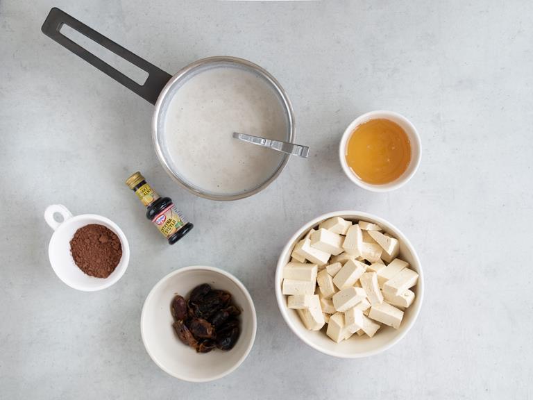 Mleko migdałowe w garnuszku, agar, pokrojone tofu, odsączone daktyle i kakao w osobnych miseczkach i Ekstrakt cytrynowy Dr. Oetkera