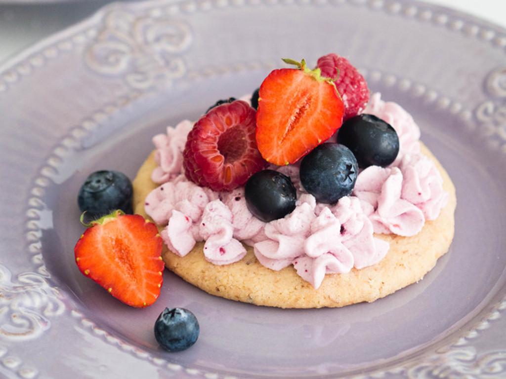 leśny mini deser na migdałowym spodzie z kremem oraz truskawkami, borówkami i migdałami