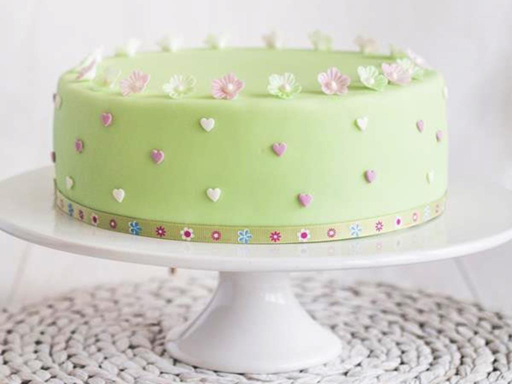 tort z masą cukrową, z cukrowymi serduszkami i kwiatkami z opłatka