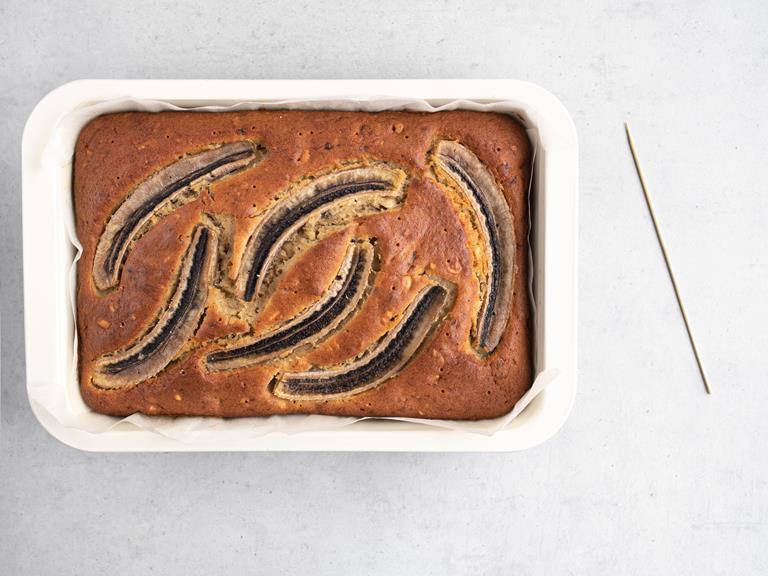 Upieczone ciasto bananowe ze zrobionymi dziurkami patyczkiem do pieczenia.