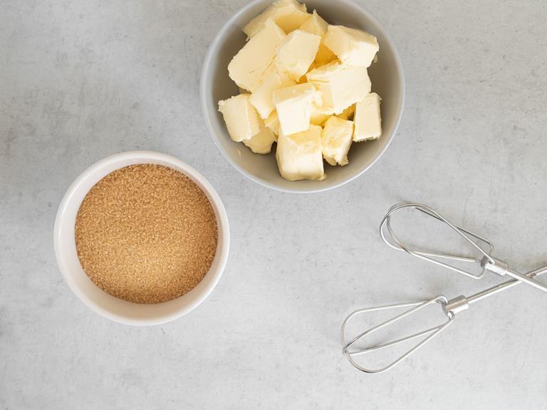 Masło i cukier trzcinowy w miseczkach.