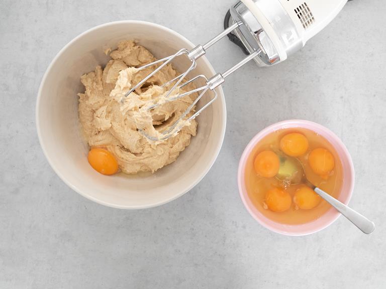 Utartce masło z cukrem w jednej misce, a w drugiej jajka.