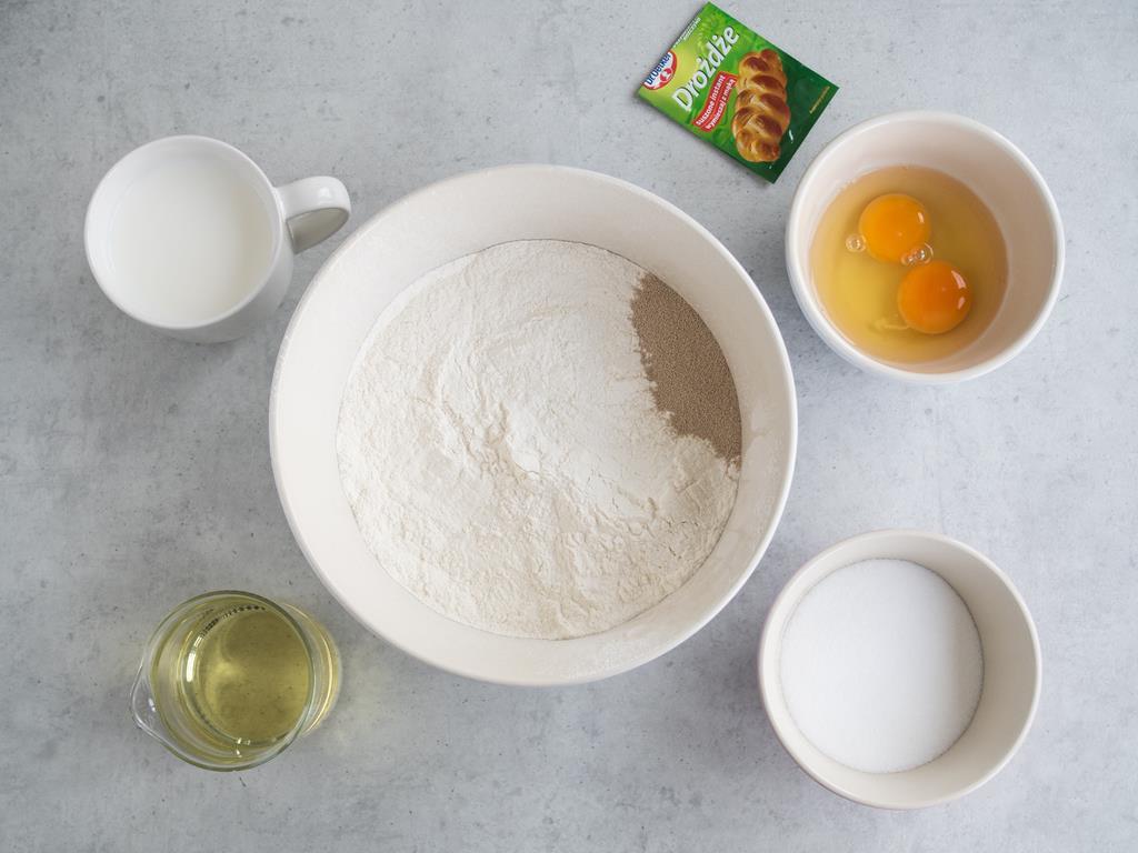 Mąka pszenna z drożdżami i szczyptą soli w miesce. Obok cukier, ciepłe mleko, olej i jajka w osobnych miseczkach.