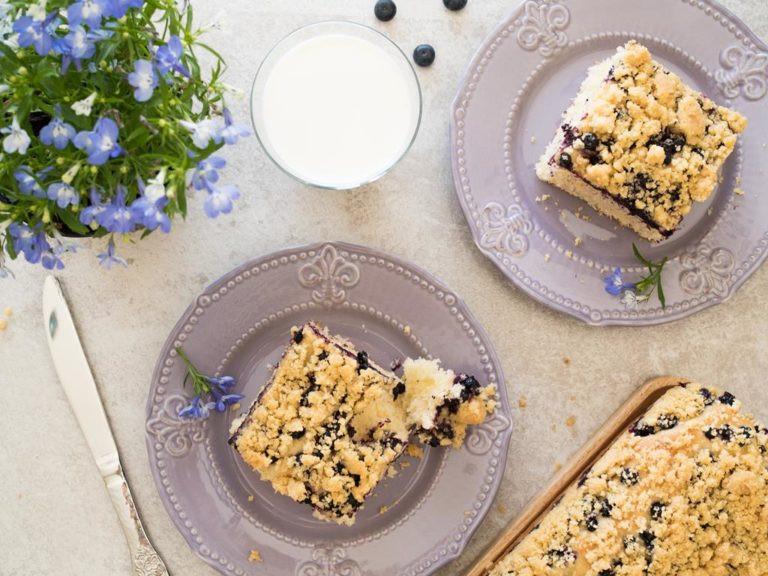 Ciasto drożdżowe z jagodami podane na fioletowych talerzykach, Obok w szklance mleko i kwiaty.