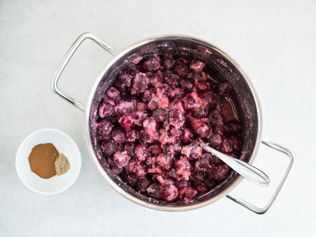 Wydrylowane wiśnie w garnku wymieszane z cukrem żelującym. Obok miseczka z cynamonem i kardamonem.