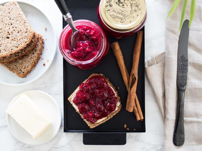 Dżem wiśniowy z cynamonem i kardamonem na kromce chleba i w słoiku, z laskami cynamonu.