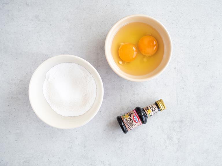 Ekstrakt waniliowy Dr. Oetkera i cukier puder oraz jajka w miseczkach.
