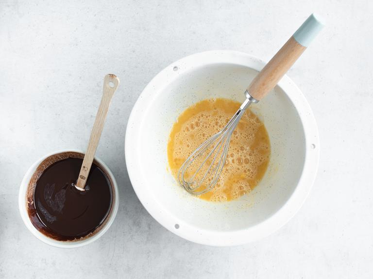 Rozpuszczona czekolada z masłem oraz masa jajeczna w miskach.