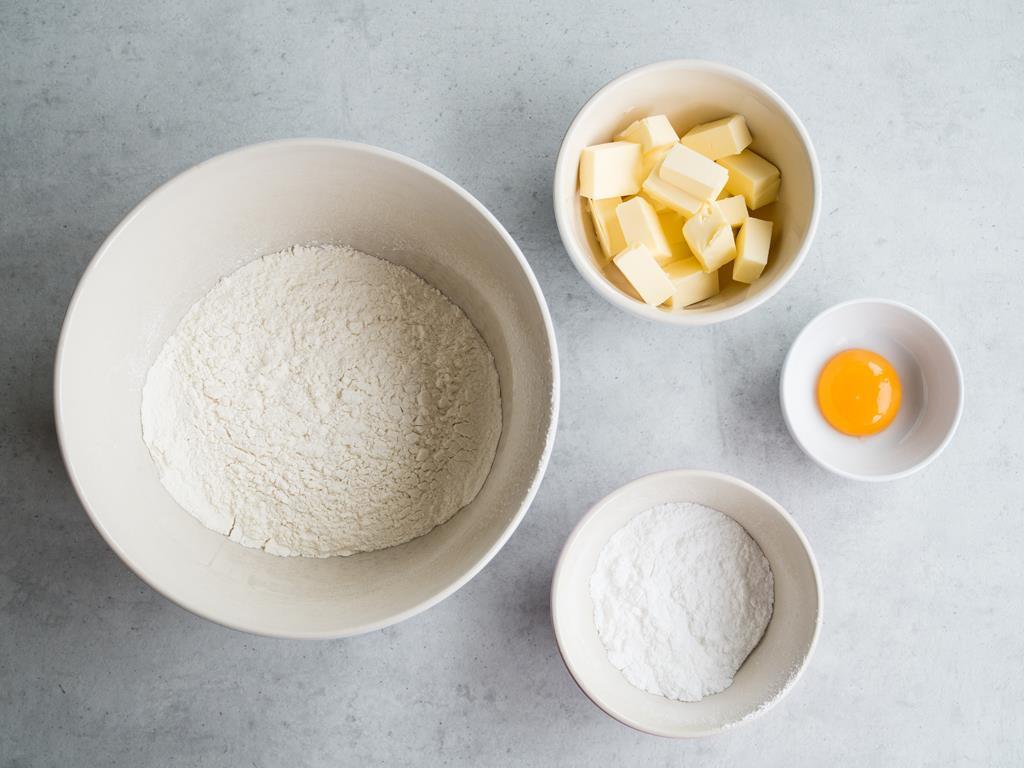 Mąka pszenna, cukier puder, masło, żółtko w osobnych miseczkach.