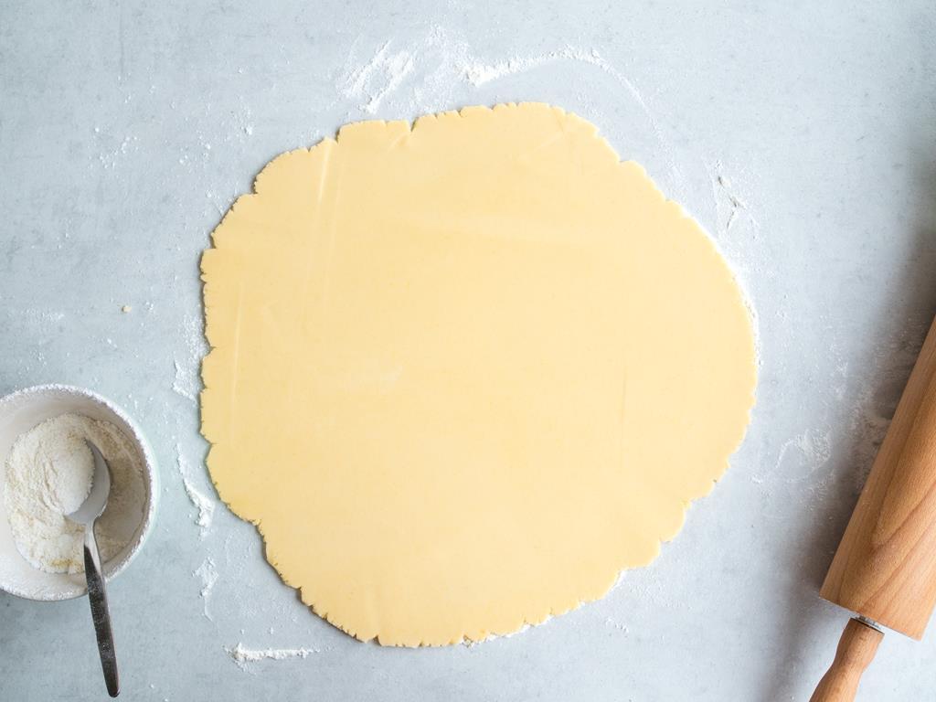 Rozwałkowane ciasto na blacie posypanym mąką.