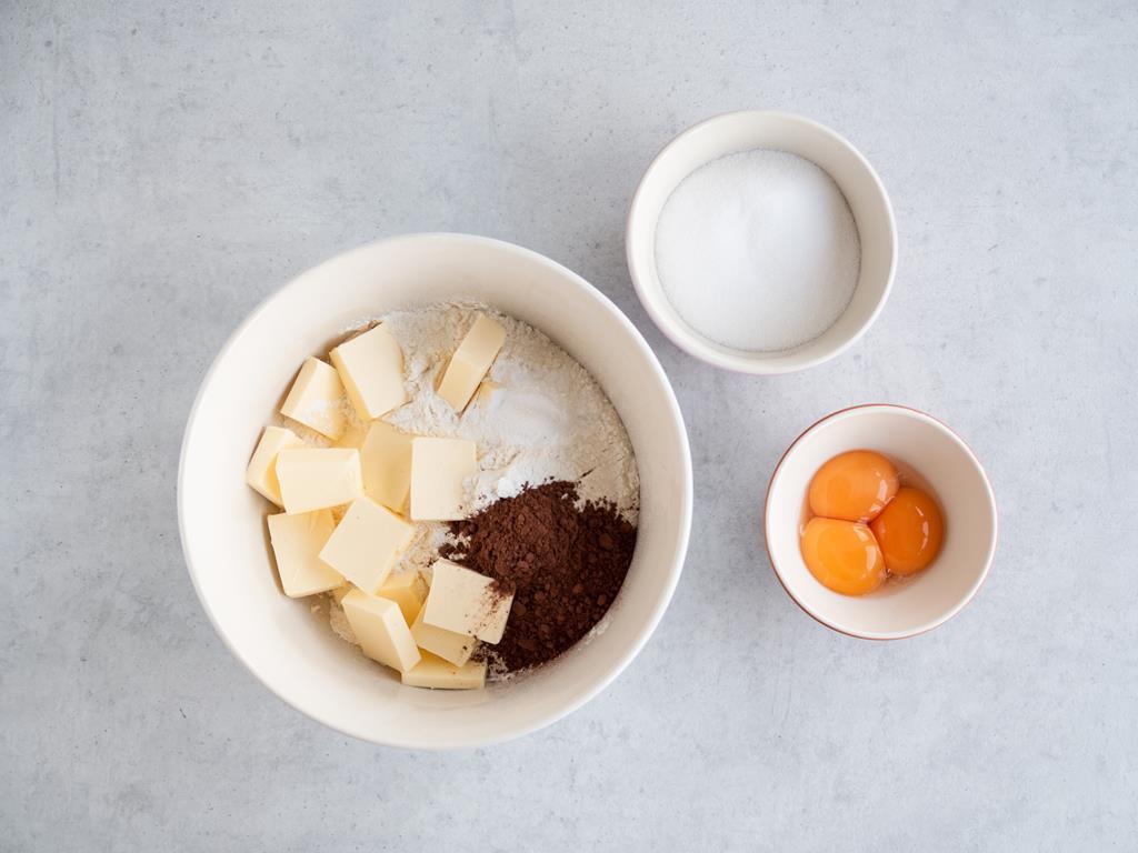 Masło, kakao, proszek do pieczenia i mąka w misce. Obok cukier i żółtka w miseczkach.