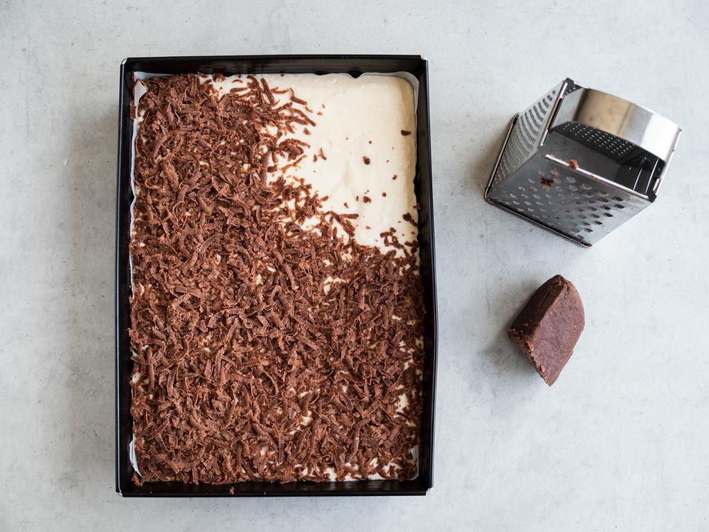 Posypywanie wierzchniej warstwy sernika ciastem kakaowym.